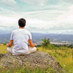 Hombre sentado en una piedra está meditando en la naturaleza
